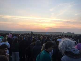 Crowds of people watching the sunrise at Stonehenge